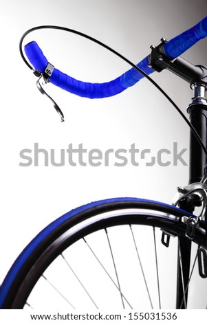 Detail on a handlebar and wheel of a race bicycle - stock photo