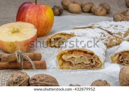 Detail on a One Slice Sugared Homemade Apple Strudel on Baking Paper - stock photo