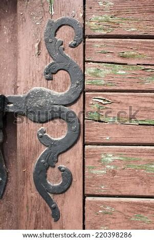 detail on ancient door, artistic handmade metallic hinge - stock photo