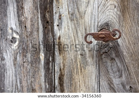 detail on old rotten door with rusty handle, focus on right