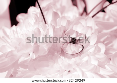 Detail on wedding rings with white flowers in red coloring