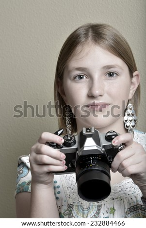 Detail portrait of young girl teenager photographer holding vintage old camera shooting photographs - stock photo