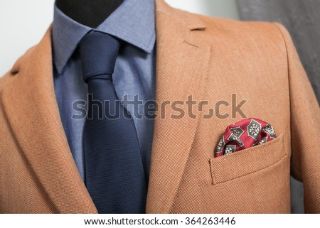 detail shot of a business shuit: blue shirt, navy tie and light brown coat - stock photo