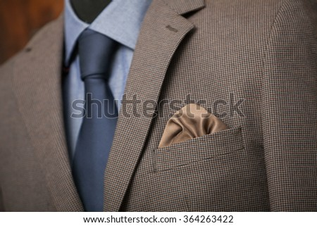 detail shot of a business suit: blue shirt, navy tie and brown coat - stock photo