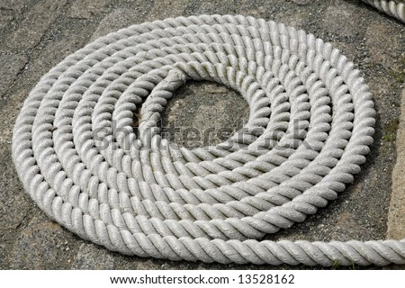 Detail shot of a coiled white rope in a harbor, used as a ship tie-down.