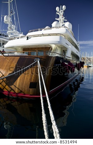 Detail shot of a nice wooden luxury yacht, locked with big cords at harbor of Monaco. - stock photo