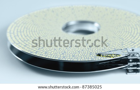 detail shot of a separated hard disk platter with actuator arm in light blue ambiance Allegory theme around information technology and data processing