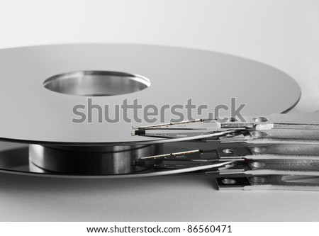 detail shot of a separated hard disk platter with actuator arm in light grey back - stock photo