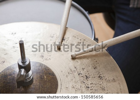 Detail shot of drumsticks on metal cymbal - stock photo