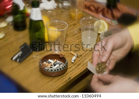 detail shot of human hands preparing a marijuana cigaret in a party - stock photo
