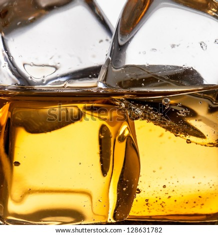 Detail shot of whiskey with ice cubes - stock photo