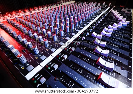 detail sound mixer in red and blue light with great perspective - stock photo