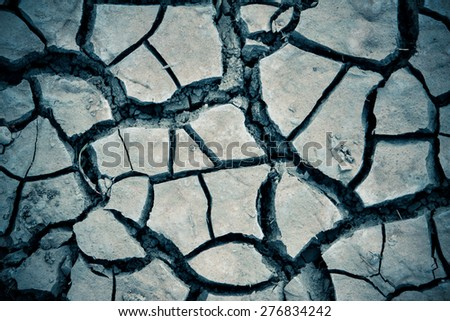 Detail texture of a dried cracked earth soil - stock photo