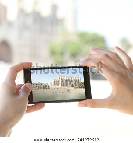 Detail view of a young woman hands holding a smartphone device up and taking photos of a monument cathedral visiting a destination city on holiday. Vacation travel technology lifestyle networking. - stock photo