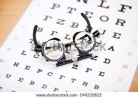 detail view of an instrument lying on snellen test chart - stock photo