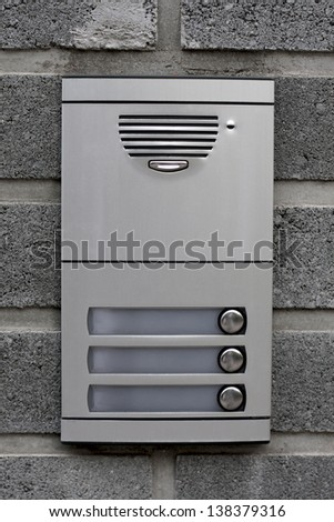 Detail view of door bell on brick wall - stock photo
