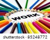 Detail view of many colored pencils arranged in circle on the word work - stock photo