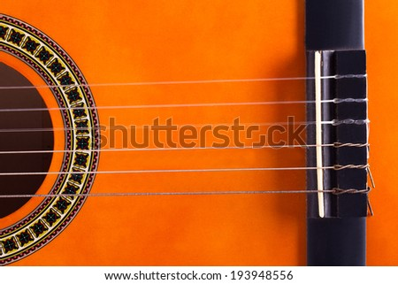 Detail view of orange wooden classical acoustic guitar. - stock photo