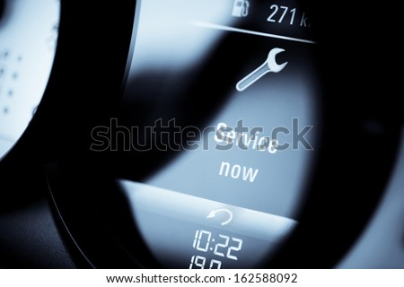 "Detail with a warning icon on the dashboard of a car reading ""Service Now"". - stock photo"