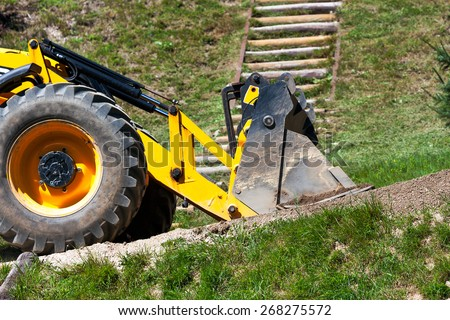 detail yellow excavator traveling on the road - stock photo