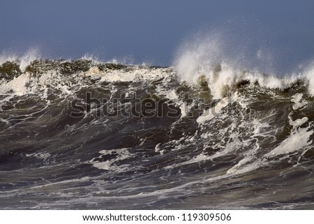 Detailed big wave on the Portuguese coast in a sunny but stormy autumn morning - stock photo