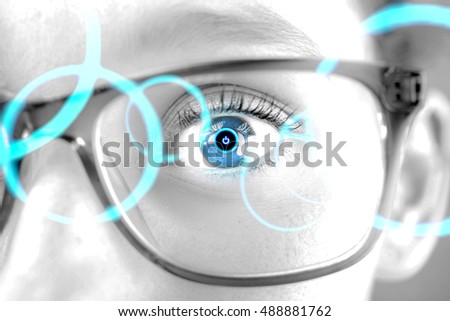 Detailed close up view of an brown eye behind glasses in high definition