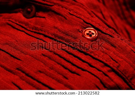 Detailed closeup macro of red button on red shirt - stock photo