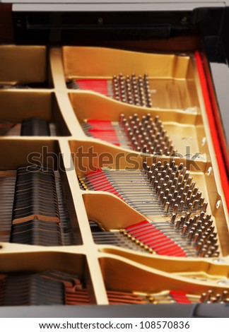 Detailed interior of grand piano showing the strings, pegs, sound board with focus on one section - stock photo