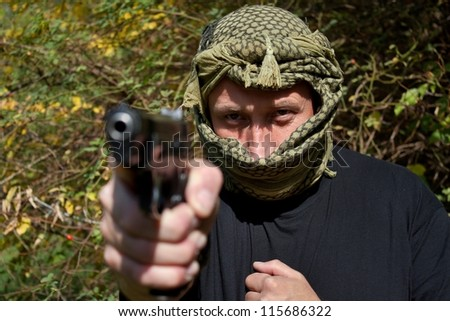 detailed look into the eyes killer pointing a gun - stock photo