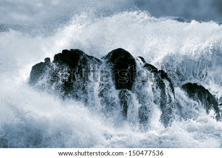 Detailed photo of a big stormy wave crashing over a boulder - stock photo