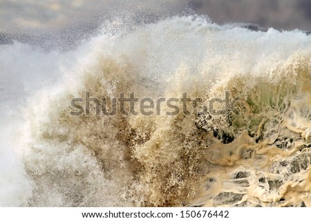 Detailed photo of a big stormy wave crashing over the coast - stock photo