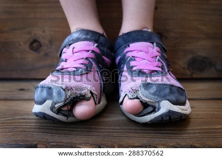 Detailed photo of shoes with holes in them and toes sticking out child kid young - stock photo