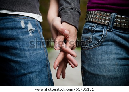 Detailed view of a young couple holding hands - stock photo