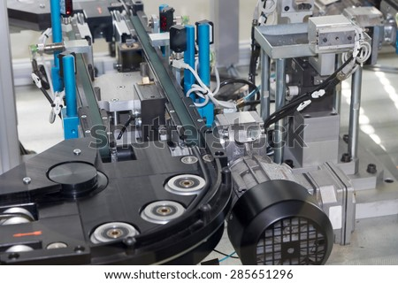 Detailed view of an empty assembly line for the production of plastic components. Horizontally. All potential trademarks are removed. - stock photo