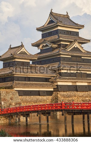 Detailed view of Matsumoto Samurai Castle, view across red bridge and moat - Matsumoto Castle is a National Treasure of Japan, Nagano Prefecture, Japanese Alps - stock photo