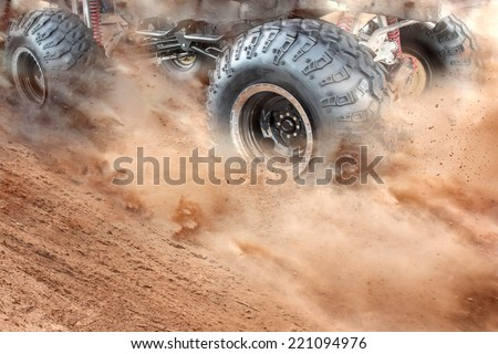 Detailed view of motion the wheels tires and off-road truck shaft that goes in the dust of the desert  through the wheels on the sand - stock photo