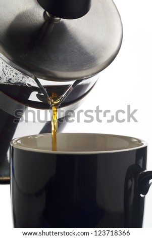 Detailed view of pouring coffee from press pot to mug - stock photo