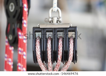 Detaill photo of a pulley with red rope - stock photo
