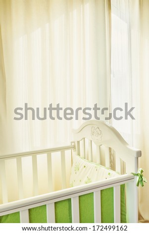 Details of a bed for babies, white curtain in the background. - stock photo