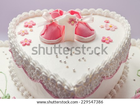 Details of a birthday cake for baby girl, number one and sweet sugar shoes on top.  - stock photo