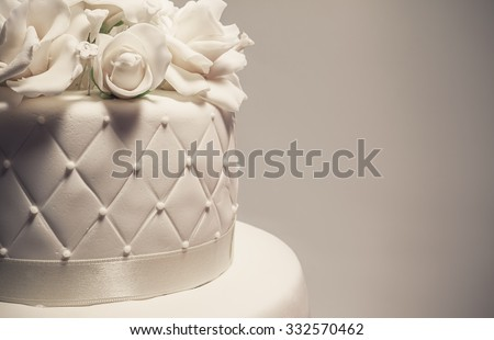 Details Of A Wedding Cake Decoration With White Fondant On Grey Background