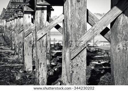 Details of a wooden walkway over the estuary at Lossiemouth in Scotland, in black and white tones - stock photo