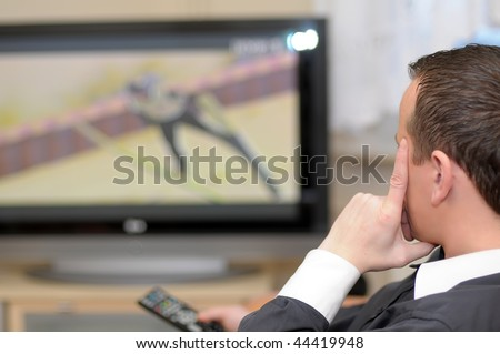 Details of a young man sitting in front of TV and holding a remote control. - stock photo
