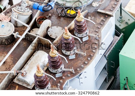 details of broken high voltage power transformer at repair shop - stock photo