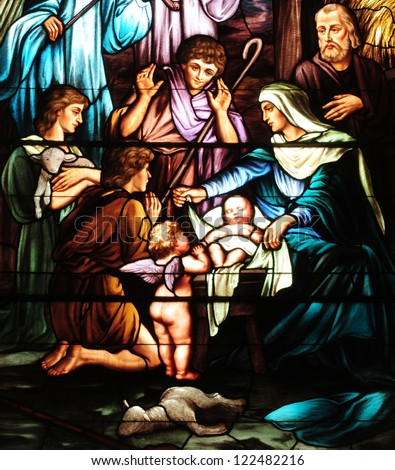 Details of Christmas stained glass window depicting birth of Jesus, with Mary, Joseph and shepherds - stock photo