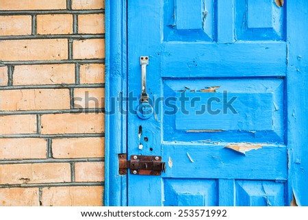 details of closed shabby blue wooden door in brick wall - stock photo