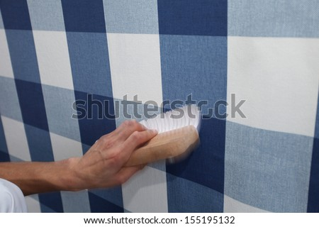 details of decorator hanging wallpaper with work tool in motion - stock photo