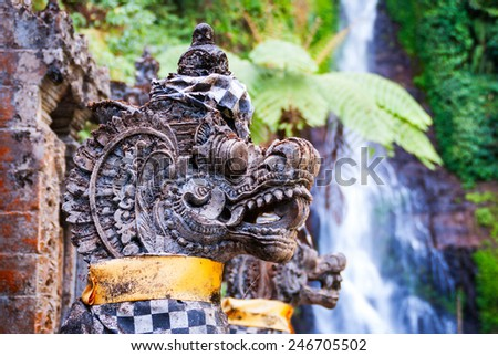 Details of dragon statues at hindu temple with waterfall behind. Gitgit, Bali, Indonesia - stock photo