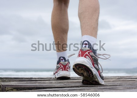 Details of feet of runner in front of a beach - stock photo