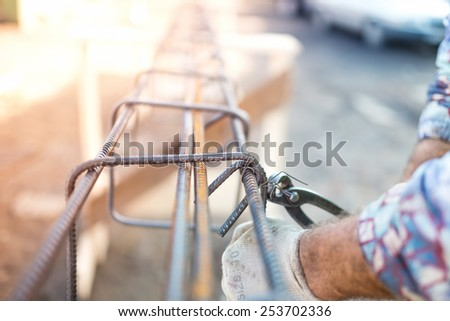Details of infrastructure - Construction worker hands securing steel bars with wire rod for reinforcement of concrete - stock photo